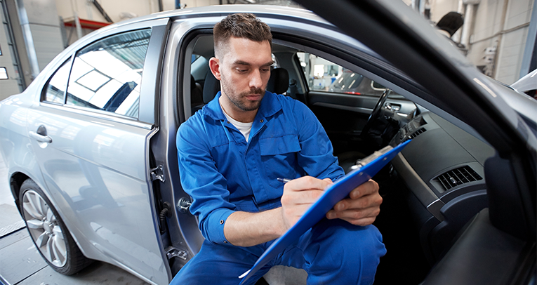 Technician checking Car MOT Testing list on a clipboard - MOT Wirral